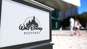 Street signage board with Walt Disney Pictures logo. Blurred office center and walking people background. Editorial 4K
