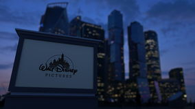 Street signage board with Walt Disney Pictures logo in the evening. Blurred business district skyscrapers background. Editorial 4K clip ProRes stock video