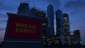 Street signage board with Wells Fargo logo in the evening. Blurred business district skyscrapers background. Editorial. 3D United States Royalty Free Stock Photography