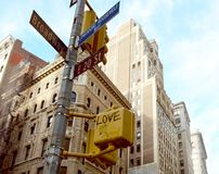 Street signs at corner of East 20th Street and Broadway. Street signs at the corner of East 20th Street and Broadway, with crossing light graffitied with the stock photography