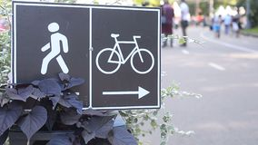 Street signs of directions for bicyclists and pedestrians. In summer park stock footage