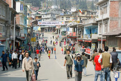 A street in Sikkim, India. Sikkim, India - People walk up and down a steet in Sikkim, India, with shops open and a banner over the street in the distance Royalty Free Stock Image