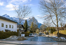 A street of a small Alpine town and ski resort with typical houses, road and mountains Royalty Free Stock Photo