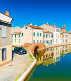 A street of the small Italian town of Comacchio, Italy. A street of the small Italian town of Comacchio. Colored houses reflected in water. Stone bridge and Stock Photos