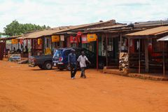 Street of a small provincial African town of Mbala in the west of Zambia. Trading tents and a street covered with orange sand royalty free stock photo