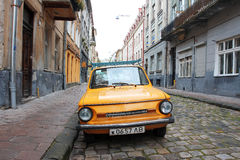 Street with small yellow car Stock Images