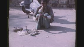 Street Snake Charmer. INDIA, DELHI, MARCH 1977. Street Snake Charmer Hitting His Lazy Cobra To Get Up From A Wicker Basket For A Snake Flute, A Been, Hypnotizing stock footage