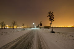 Street through snow in winter with city lights on horizon Royalty Free Stock Images