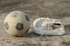 Street soccer equipment. Soccer ball with canvas shoes on concrete floor (street soccer Stock Image