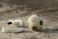 Street soccer equipment. Soccer ball with canvas shoes on concrete floor (street soccer background Royalty Free Stock Images
