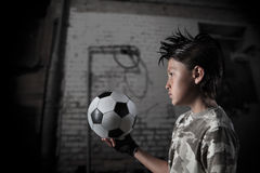 Street Soccer Series. A young boy plays street soccer against a graffiti covered wall - with dramatic lighting and subdued colors Royalty Free Stock Image