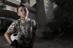 Street Soccer Series. A young boy plays street soccer against a graffiti covered wall - with dramatic lighting and subdued colors Royalty Free Stock Photography
