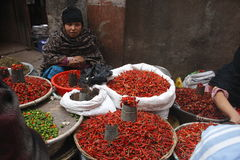 Street spices shop. Woman with baskets of red chilli pepper, sitting on the street in center of Kahmandu - Thamel, january 2009, Nepal Stock Photos