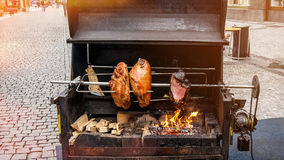 Street spit for cooking roast shank in Prague on a Sunny day. The horizontal frame Royalty Free Stock Photography