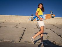 Street sports: a cheerful girl in a yellow T-shirt walks with a longboard pintail on a concrete embankment. Portrait. Royalty Free Stock Photography