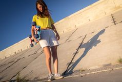Street sports: a cheerful girl in a yellow T-shirt walks with a longboard pintail on a concrete embankment. Royalty Free Stock Photography