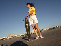 Street sports: A girl in a bright yellow T-shirt is holding a large longboard pintail against the backdrop of the city. Royalty Free Stock Photography