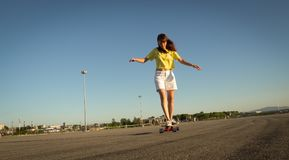Street Sports: A girl in a bright yellow T-shirt is rolling on a longboard on the city`s asphalt. Stock Image