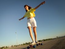 Street Sports: A girl in a bright yellow T-shirt is rolling on a longboard on the city`s asphalt. Stock Images