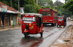 On The Street In Sri Lanka. Three-wheelers and the bus on the street in Sri Lanka in the north of the country on a rainy day. At this very time the Government Royalty Free Stock Photography