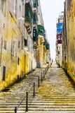 Street with stairs in Valletta. Typical narrow street with stairs on the island of Malta. Buildings with traditional colorful maltese balconies in historical stock photo