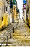 Street with stairs in Valletta. Typical narrow street with stairs on the island of Malta. Buildings with traditional colorful maltese balconies in historical royalty free stock image
