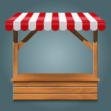 Street stall with red awning and wooden rack. Royalty Free Stock Photo