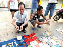 The street stall, selling old books and ancient coins. People are watching, and buying Stock Photos