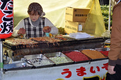 Street Stall Selling Takoyaki. A woman mans her street stall, cooking and selling octopus balls (takoyaki) a popular snack in Japan stock image