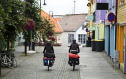 Street of Stavanger, cyclists. A perspective of Stavanger street, a famous Norwegian city, popular tourist destination. Two cyclists riding along the street royalty free stock images