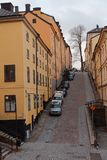 Street on Stockholm hills. Stockholm, Sweden - November 27, 2016: Cars on the steep hill on Brannkyrkagatan street. This hill with slope of 22% was used in the Royalty Free Stock Image
