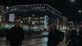 Street with Stockmann shopping mall, tram and people traffic in night Helsinki. HELSINKI, FINLAND - JANUARY 07, 2017: Night city view with Stockmann shopping stock video