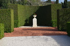 Street stone vase on a stone pedestal against the living-trimmed hedges Stock Image