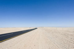 Street straight through the desert in Namibia Royalty Free Stock Images