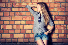 Street Style Fashion Girl at the Brick Wall Royalty Free Stock Images