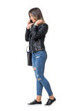 Street style fashion girl walking while talking on the phone and adjusting hair. Stock Photo