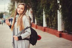 Street style portrait of young beautiful happy girl walking in autumn city Royalty Free Stock Photos