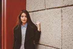 Street style portrait of young feminine girl in black coat Stock Photos