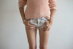 Street style posing girl in short jeans shorts and pink pullover Royalty Free Stock Photos
