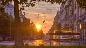 Street with sunset in the Croatian capital Zagreb. People sitting on the bench near tree stock footage