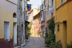 Street with sunshine in Villefranche-sur-Mer. Sunny narrow street with colorful old buildings and green potted plants in medieval town Villefranche-sur-Mer on Royalty Free Stock Photos