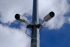 Street surveillance cameras. Two surveillance cameras on the same support on the street under the sky Royalty Free Stock Photography