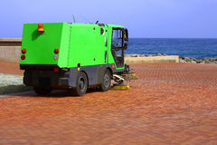 Street sweeper. A green Street Sweeper near the city beach on blue sky day Stock Photos