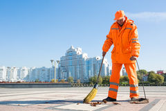 Street sweeper cleaning city sidewalk. Man road sweeper caretaker cleaning city street with broom tool Royalty Free Stock Photo