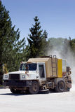 Street sweeper with dust trail. A street sweeper truck with a dust cloud behind Stock Photography