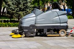 Street sweeper machine cleaning walkways in park. Street sweeper machine cleaning walkways in the park Royalty Free Stock Images