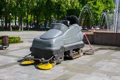 Street sweeper machine cleaning walkways in the park. Street sweeper machine cleaning walkways in the city park Stock Photo