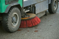 Street sweeper machine. A close up of wheels and brush of a street sweeper machine Stock Image