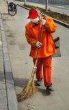 Street sweeper in orange garb on street. Beijing, China - April 26, 2010: Closeup of street sweeper in orange garb and white mouth mask in action with twig royalty free stock photos