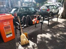 A street sweeper naps on a bench, Tel Aviv, Israel royalty free stock image